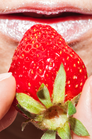 Strawberry in hand close-up. Womans mouth with red strawberry Zdjęcie Seryjne