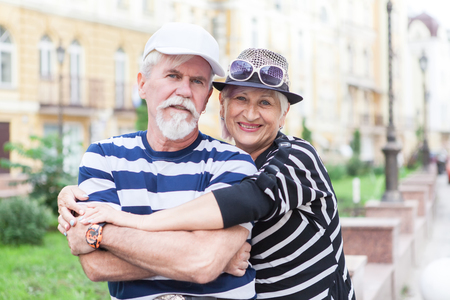 Happy friendly senior couple posing arm in arm with their faces touching smiling at the camera Stock Photo
