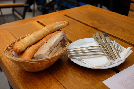 breakfeast: On the table is a basket of bread, a plate with knives and forks