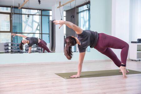 Photo de jeune femme pratiquant le yoga à l'intérieur. Belle fille pratique le yoga en classe. Instructeur de studio de yoga. Arrière-plan flou.