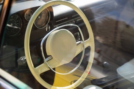 Photo of interior of vintage car with light saloon and details. Old car classic concept.