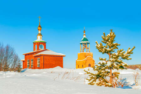 Small wooden Russian Orthodox church and bell tower in an early winter evening. Arkhangelsk Oblast. Russia