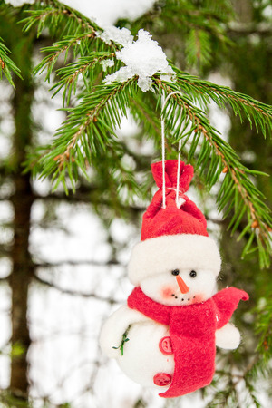 coldly: Toy snowman hanging on a snow-covered tree