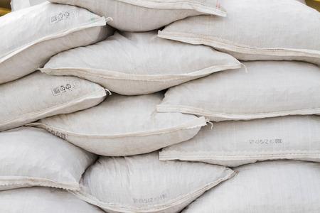 materiales de construccion: Bolsas blancas de arena en la base de una construcción abierta