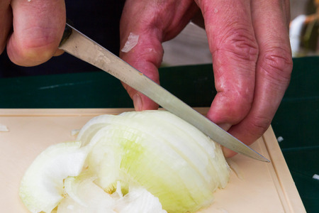 cuchillo de cocina: Sliced onion and kitchen knife on cutting Board