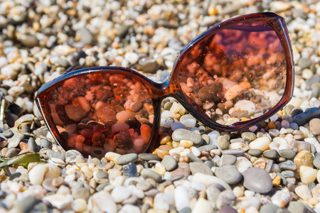 clothes interesting: Sunglasses on the beach of small pebbles