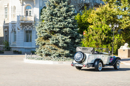 tree disc: Evpatoria, Crimea, Russia, August 30, 2015. Vintage car with open top on the square in town Yevpatoria in Crimea.