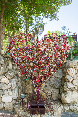 Metallic red heart hung with locks of love