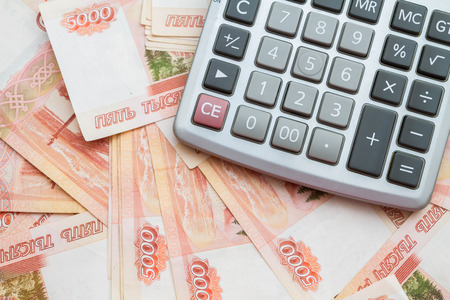 red button: The calculator lies on big Russian money Stock Photo