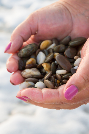 Sea stones in hands on the beach at sunset Stock Photo