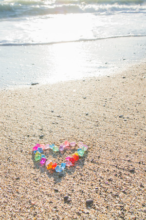Brightly colored heart of glass pebbles on the sea shore