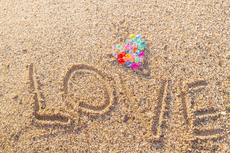 The inscription love with a colored heart on the beach Stock Photo