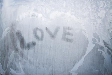 Inscription d'amour sur la fenêtre gelée en motifs d'hiver en hiver Banque d'images - 96955997