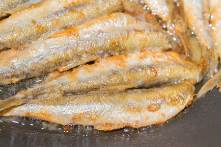 Cooking fried fish smelt rolled in flour Stock Photo