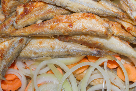 Fried fish smelt lies on the cut onion and carrot