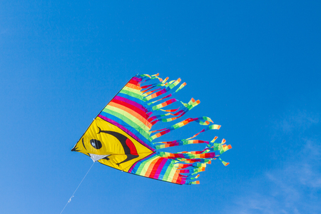 A fun and bright flying kite in the blue sky Stock Photo