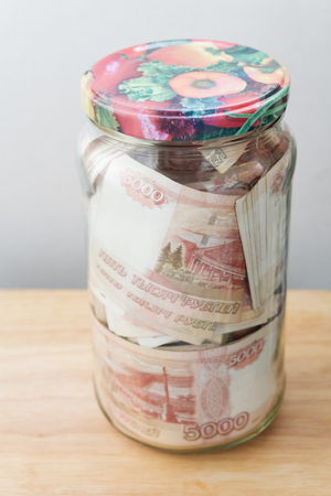 A large sum of Russian money in denominations of five thousand rubles is in a glass jar