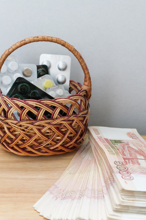 Pills and medicines are in the basket next to the big Russian money Stock Photo