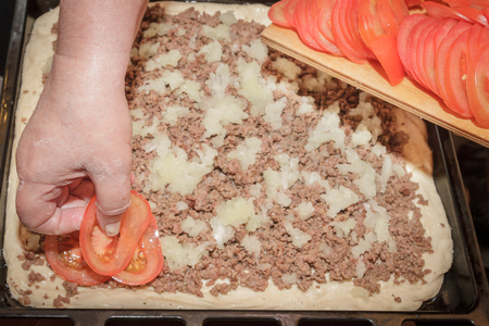 Cooking pizza pie with meat and vegetables under cheese