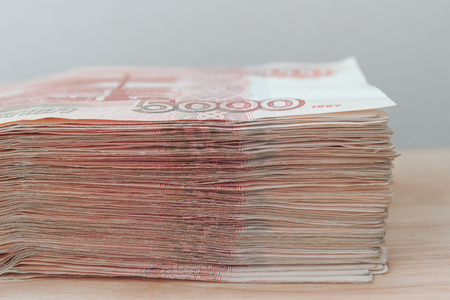 Big stack of Russian money banknotes of five thousand rubles lying on a wooden table Stock Photo