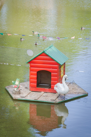 Red wooden house for a Swan on the water