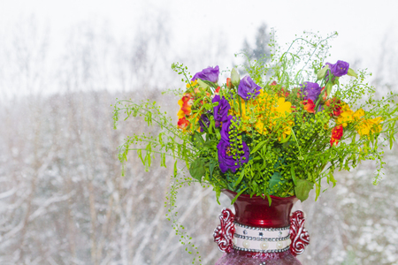 A beautiful vase of spring flowers stands on a window in a snowstorm Imagens