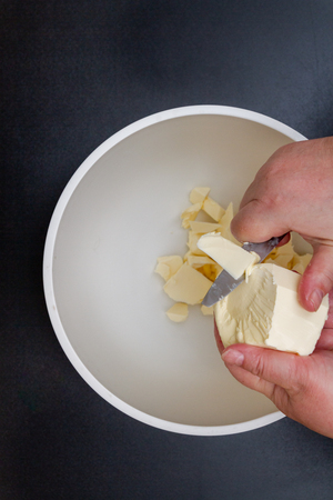Pieces of butter are in a bowl for mixing in the preparation of cookies