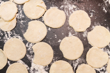 Rolled out raw dough cut into roundels on a table with scattered flour