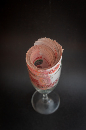 A large pack of Russian money rolled in a glass