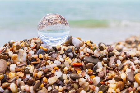Glass round ball on the beach reflects the sea in summer