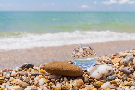 Glass round ball on the beach reflects the sea in summer Фото со стока - 129210467