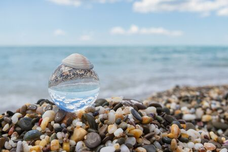 Glass round ball on the beach reflects the sea in summer Фото со стока - 129212866