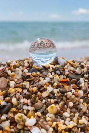 Glass round ball on the beach reflects the sea in summer Фото со стока - 129212861