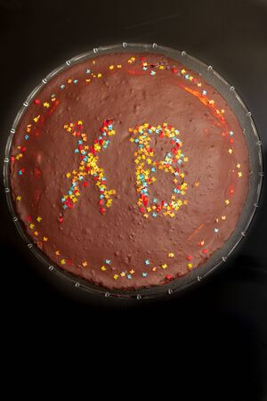 Chocolate cake at Easter with inscription of HV with colored sprinkles.