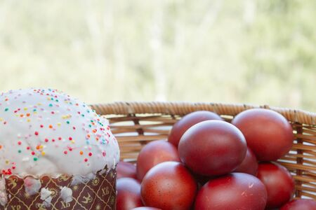 Easter spring cake with painted chicken eggs in a wicker basket