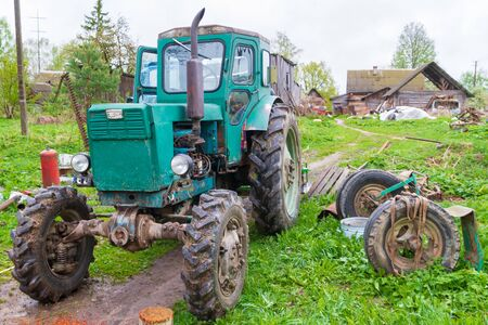 Old tractor in the village in early spring