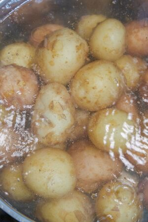 New potatoes boil in their skins in a saucepan Archivio Fotografico