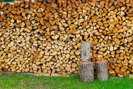 A lot of firewood stacked in a pile on the street