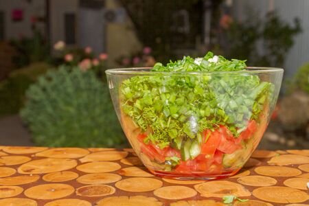Prepared salad of fresh vegetables and herbs in a glass bowl