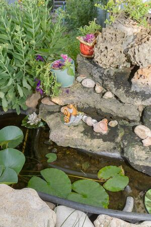 Landscape decoration in the form of a fountain with a snail and shells in the yard