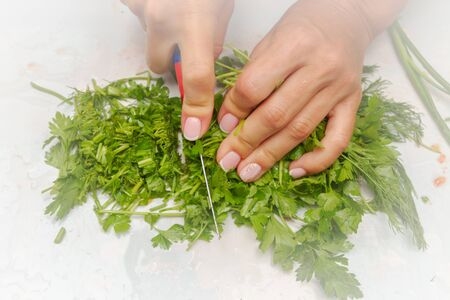 Cutting fresh greens and green onions on a white cutting Board