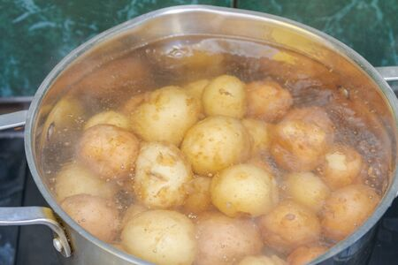 New potatoes boil in their skins in a saucepan Фото со стока