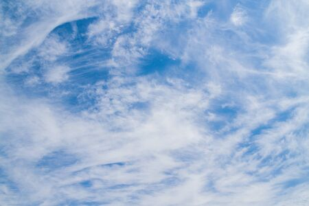 White fluffy clouds in the blue sky in summer Фото со стока