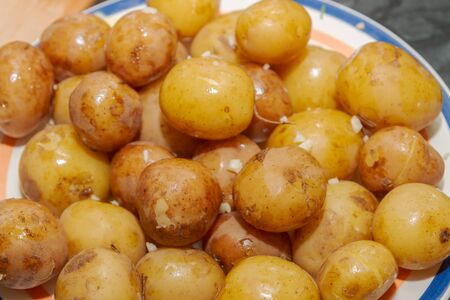 Young boiled potatoes in uniform with garlic and butter lying on a plate