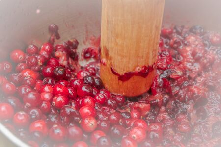 Crush the red cranberry berries with a wooden rolling pin