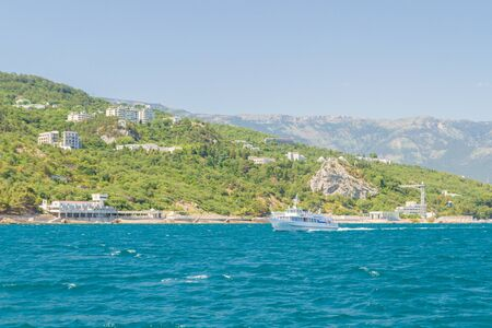 city of Yalta, Crimea, Russia 02 July 2019. White ship sailing on the sea in the summer on a Sunny day 新聞圖片