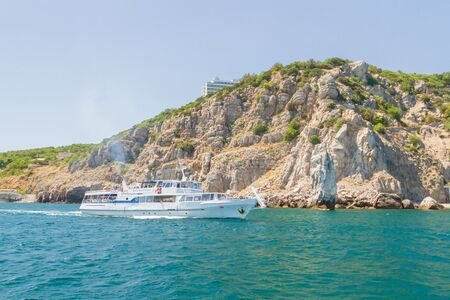 city of Yalta, Crimea, Russia 02 July 2019. White ship sails on the sea along the rocky coast in summer