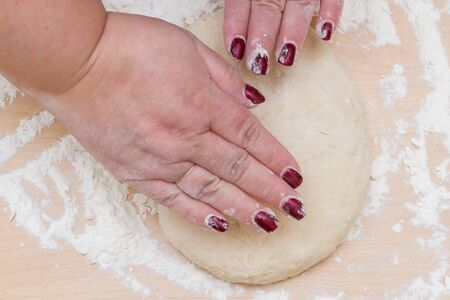 Kneading dough with flour on a wooden table at home