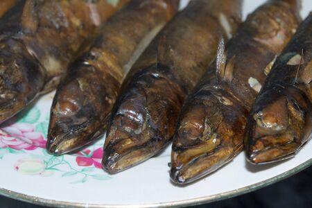Smoked fresh fish mackerel lies hot on a ceramic plate