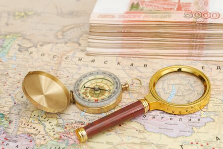 A compass with a bundle of big money and a magnifying glass are on the map